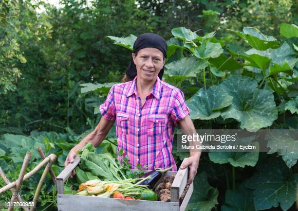 portrait of farmer holding vegetables standing against trees - south america stock pictures, royalty-free photos & images