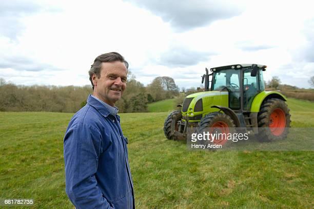 Portrait of farmer in field in front of tractor