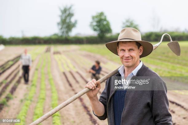 Portrait of farmer in field with hoe