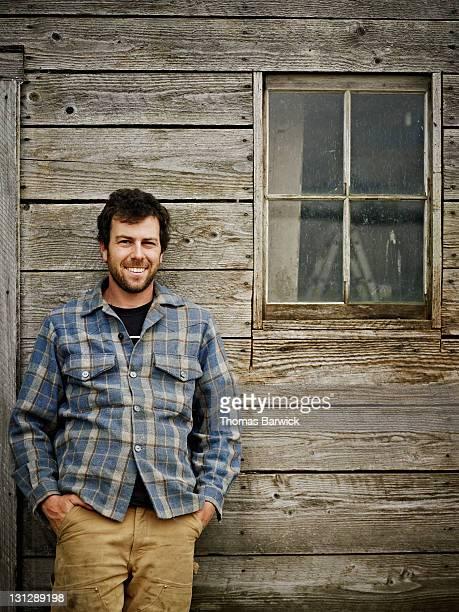 Portrait of farmer leaning against side of barn