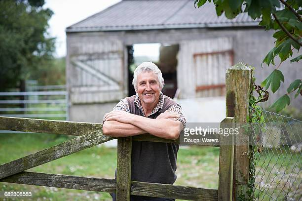 portrait of farmer leaning on fence. - farmer stock pictures, royalty-free photos & images