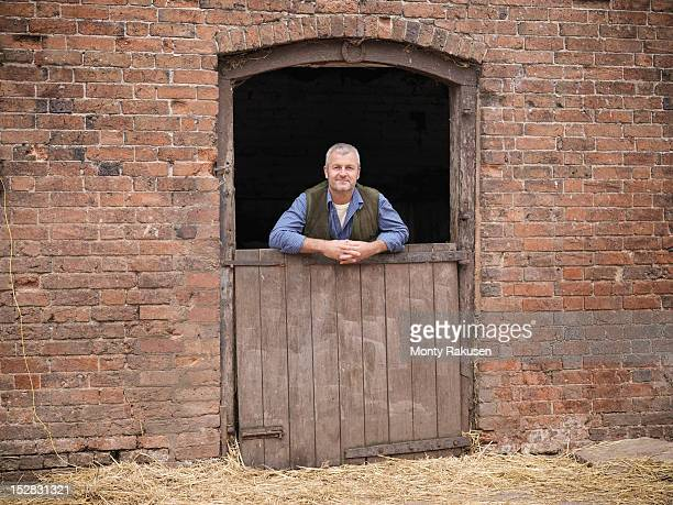 Portrait of farmer leaning on stable door
