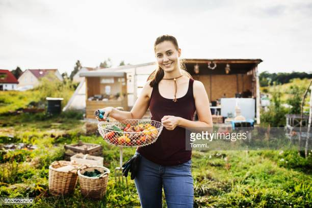 Portrait Of Farmer Smiling Holding Basket Of Tomatoes