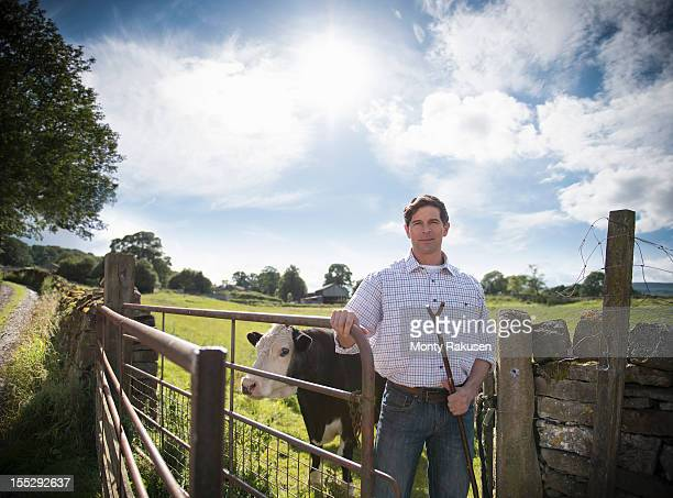 Portrait of farmer standing by gate with cow