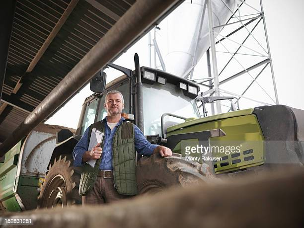 Portrait of farmer with clipboard by tractor on dairy farm