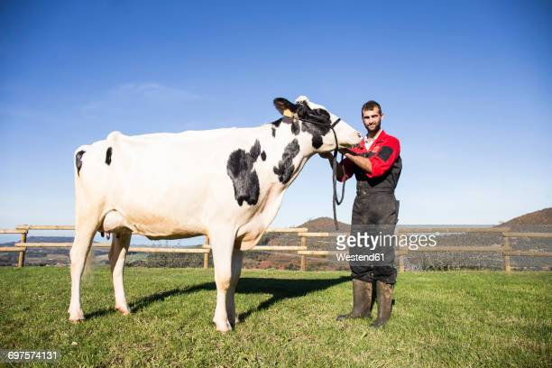 Portrait of farmer with cow on pasture