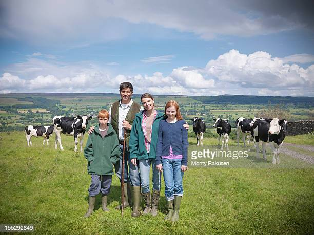 Portrait of farmer with family and cows in field