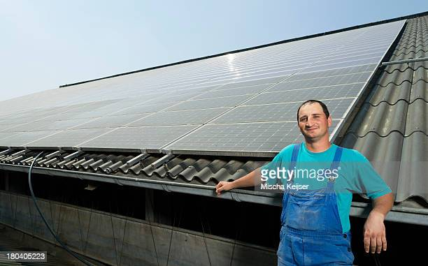 Portrait of farmer with solar panels on barn roof, Waldfeucht-Bocket, Germany