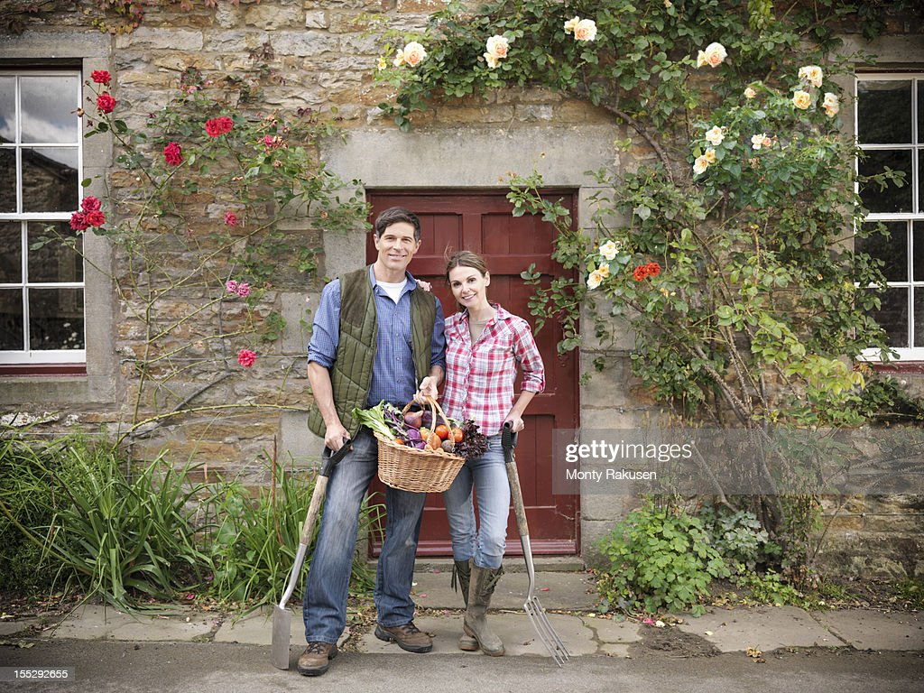 Portrait of farming couple with basket of organic vegetables and gardening tools standing in front of farmhouse doorway : Stock Photo