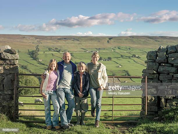 Portrait of farming family in front of gate in rural landscape