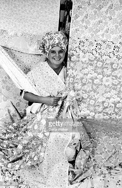 Portrait of fashion designer Lilly Pulitzer wearing head dress amidst her cotton prints