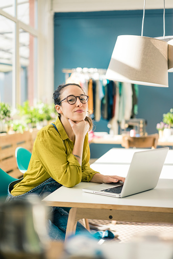 Portrait of fashion designer sitting at desk in her studio with laptop - gettyimageskorea