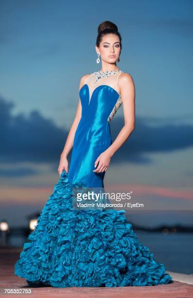 Portrait Of Fashion Model In Blue Evening Gown Standing On Pier During Sunset