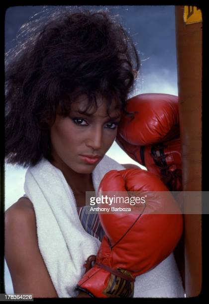 Portrait of fashion model Sheila Johnson as she poses in boxing gloves with a towel over her shoulders early 1980s