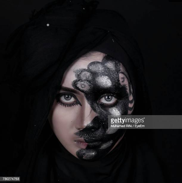 Portrait Of Fashion Model With Glitter Face Paint Against Black Background