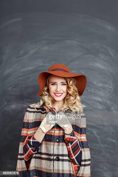 Porträt eines modischen blonde Frau stehend gegen Tafel
