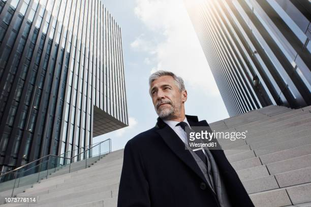 portrait of fashionable businessman in front of modern architecture - geschäftskleidung stock-fotos und bilder