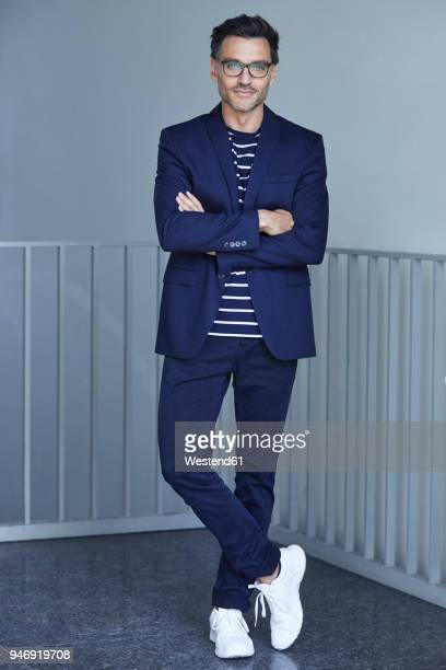 portrait of fashionable businessman with wearing blue suit and glasses - mannen stockfoto's en -beelden