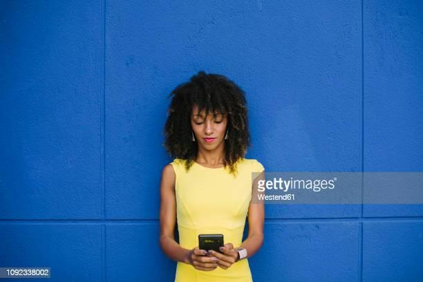 portrait of fashionable businesswoman in yellow dress text messaging against blue background - regarder vers le bas photos et images de collection