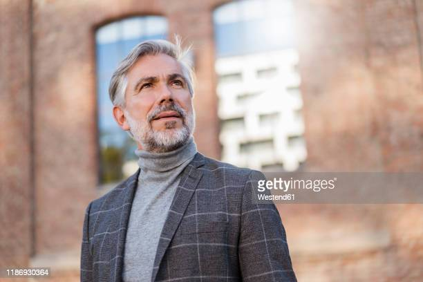 portrait of fashionable mature businessman at a brick building - gray suit stock pictures, royalty-free photos & images