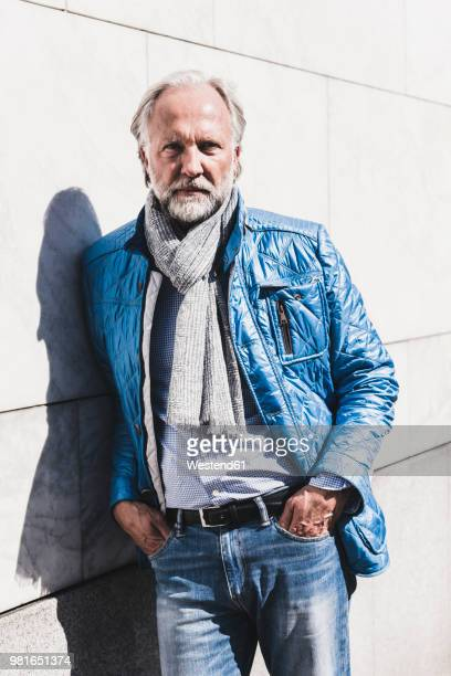 Portrait of fashionable mature man leaning against a wall