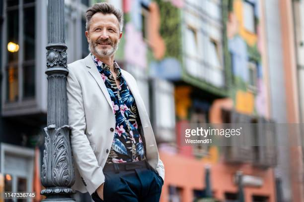 portrait of fashionable mature man with greying beard leaning against - men fashion stock pictures, royalty-free photos & images