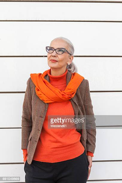 Portrait of fashionable mature woman in front of white wall