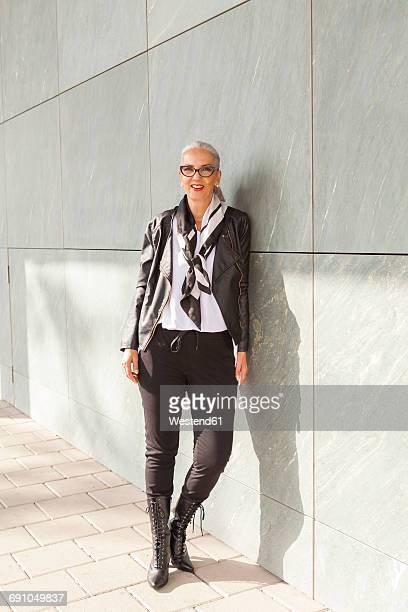 portrait of fashionable mature woman leaning against wall - black boot stock pictures, royalty-free photos & images