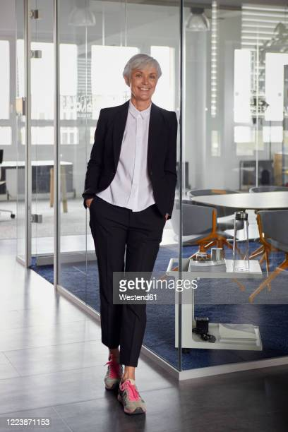 portrait of fashionable senior businesswoman wearing pantsuit and sneakers in office - leaning stock pictures, royalty-free photos & images