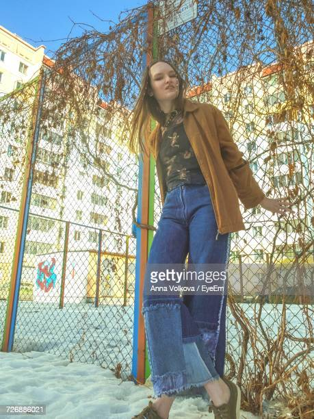 Portrait Of Fashionable Woman Standing Against Chainlink Fence During Winter
