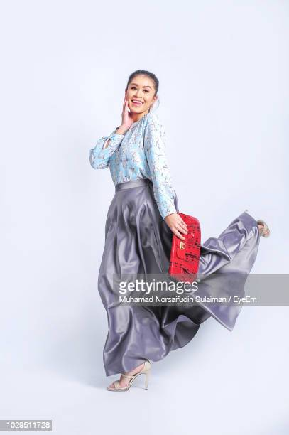 portrait of fashionable woman walking against white background - personal accessory stock photos and pictures