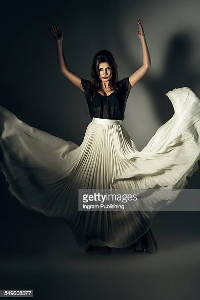 Portrait of fashionable woman with flying maxi skirt