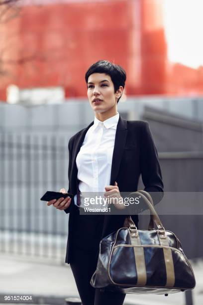 Portrait of fashionable young businesswoman with cell phone and bag