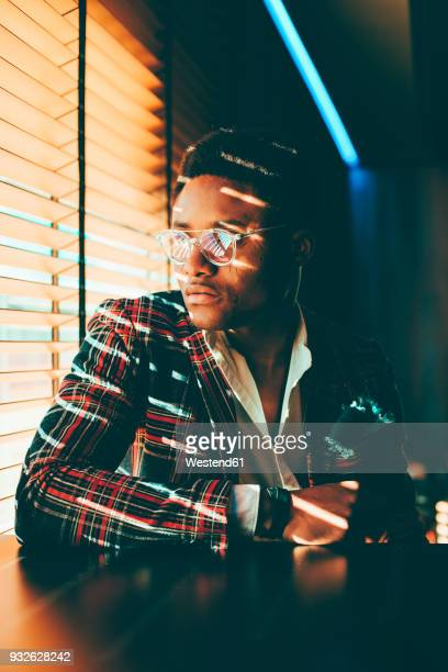 portrait of fashionable young man wearing checkered suit coat looking out of window - high contrast stock pictures, royalty-free photos & images