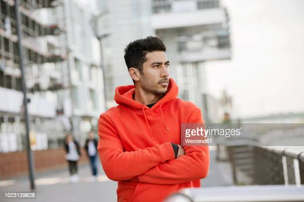 portrait of fashionable young man wearing red hooded jacket - パーカー服 ストックフォトと画像