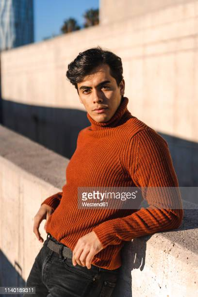 portrait of fashionable young man wearing turtleneck pullover leaning on a wall at sunlight - men fashion stock pictures, royalty-free photos & images