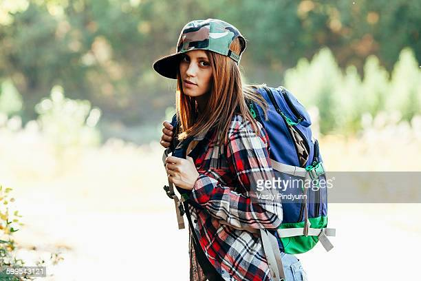 Portrait of fashionable young woman hiking in forest
