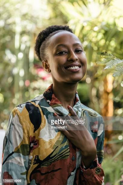 portrait of fashionable young woman in garden - flerfärgad klänning bildbanksfoton och bilder