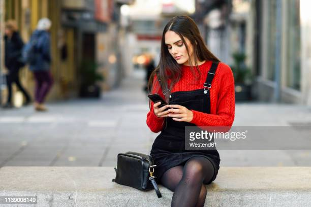 portrait of fashionable young woman sitting on bench at pedestrian area looking at cell phone - junge frau strumpfhose stock-fotos und bilder