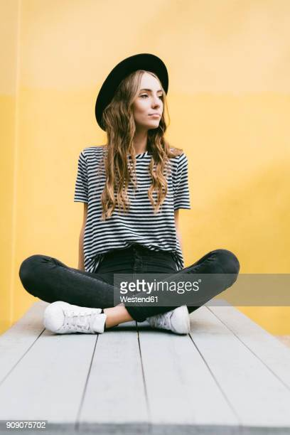 Portrait of fashionable young woman wearing hat sitting in front of yellow wall