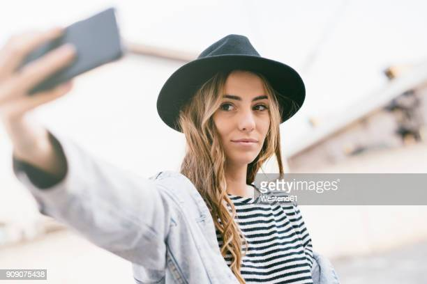 portrait of fashionable young woman wearing hat taking selfie with smartphone - selfie foto e immagini stock