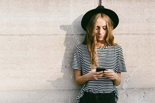 Portrait of fashionable young woman wearing hat using smartphone - gettyimageskorea