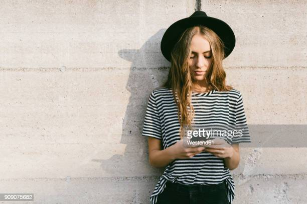 portrait of fashionable young woman wearing hat using smartphone - jonge vrouw stockfoto's en -beelden