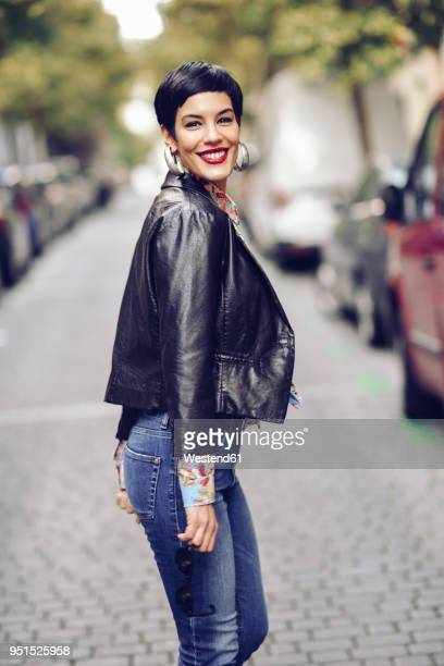 portrait of fashionable young woman wearing jeans and leather jacket - short hair stock pictures, royalty-free photos & images