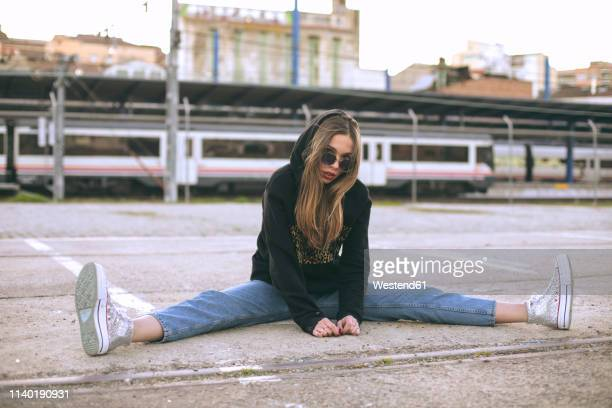 portrait of fashionable young woman wearing sunglasses and black hooded jacket - legs apart stock pictures, royalty-free photos & images