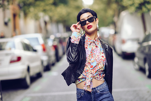 Portrait of fashionable young woman wearing sunglasses and leather jacket - gettyimageskorea