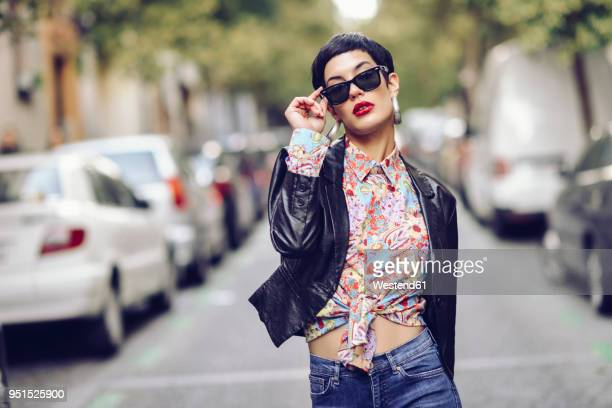 portrait of fashionable young woman wearing sunglasses and leather jacket - ontwerp stockfoto's en -beelden