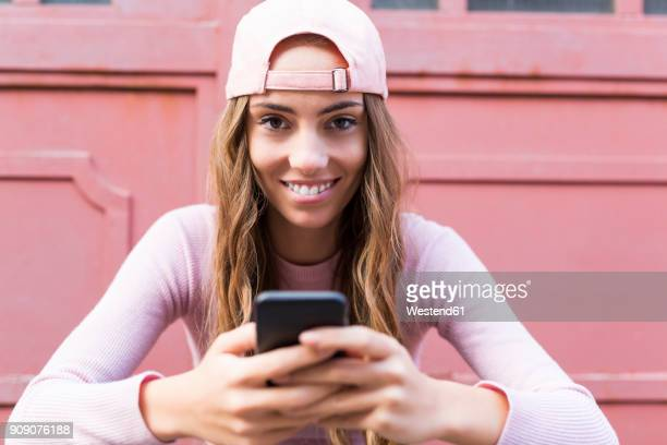 Portrait of fashionable young woman with cell phone wearing basecap