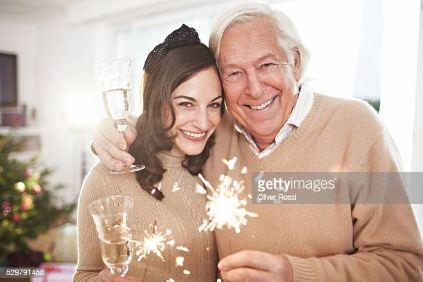 Portrait of father and adult daughter holding sparklers at Christmas