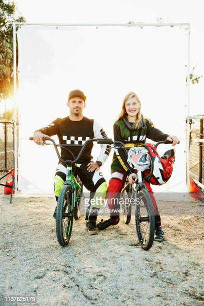 Portrait of father and daughter BMX racers sitting on bikes in front of white background